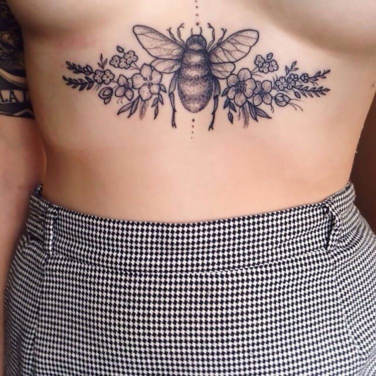 large bee tattoo across stomach
