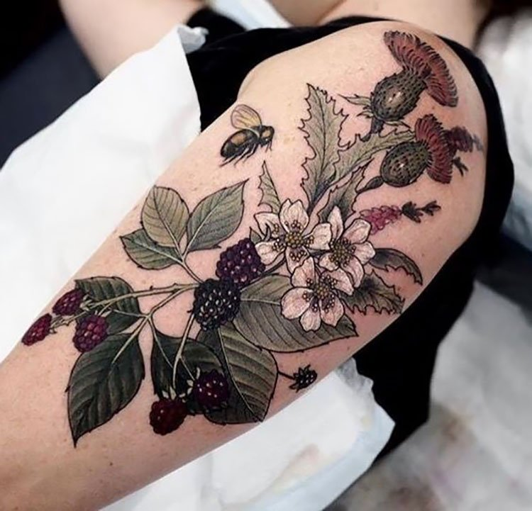 large arm tattoo bee with flowers and berries