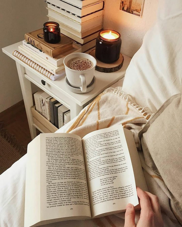 book on bed with coffee