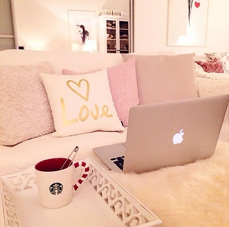 pink and white bed with coffee and laptop