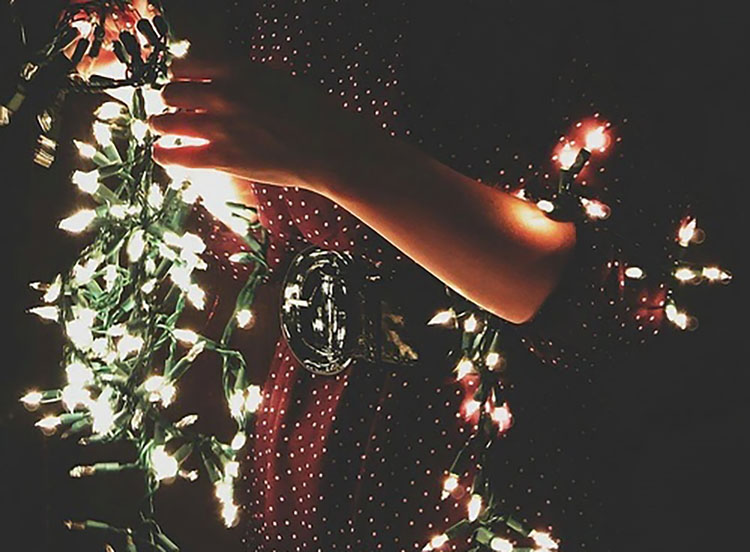 PERSON HOLDING CHRISTMAS LIGHTS
