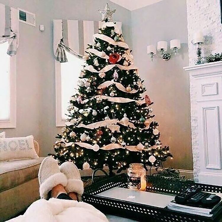 WOMAN SITTING NEAR CHRISTMAS TREE
