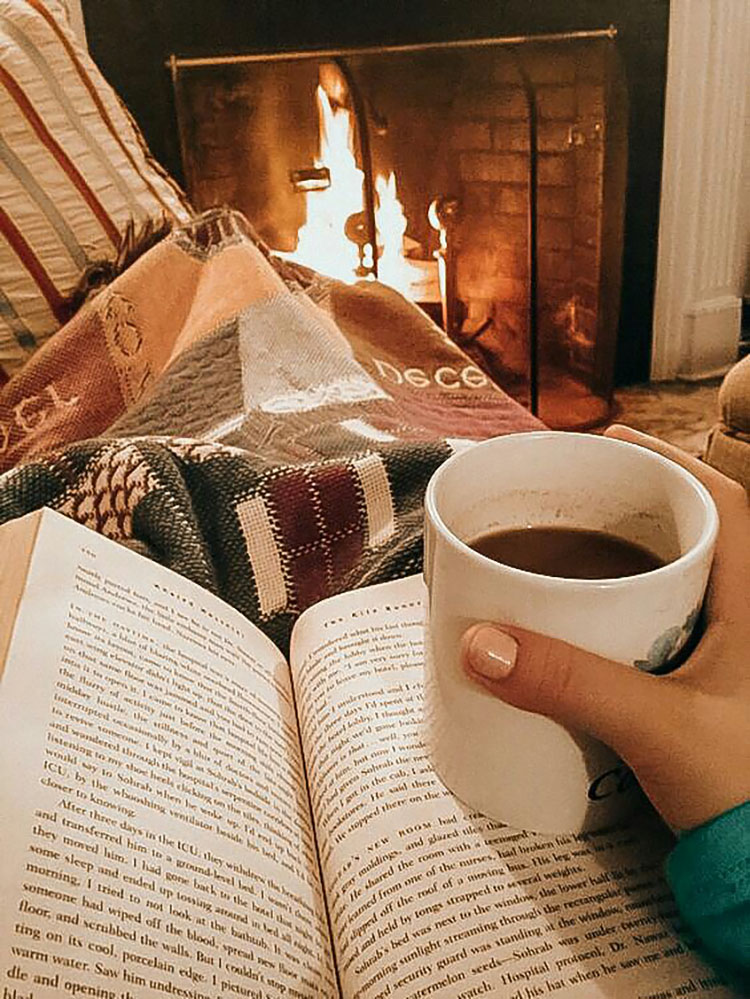 WOMAN HOLDING BOOK AND TEA