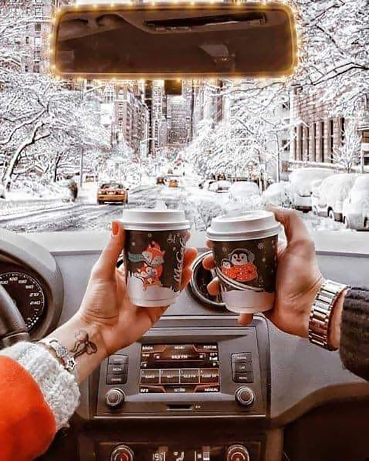 COUPLE HOLDING COFFEE CUPS IN CAR