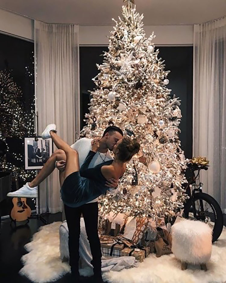 COUPLE KISSING IN FRONT OF CHRISTMAS TREE
