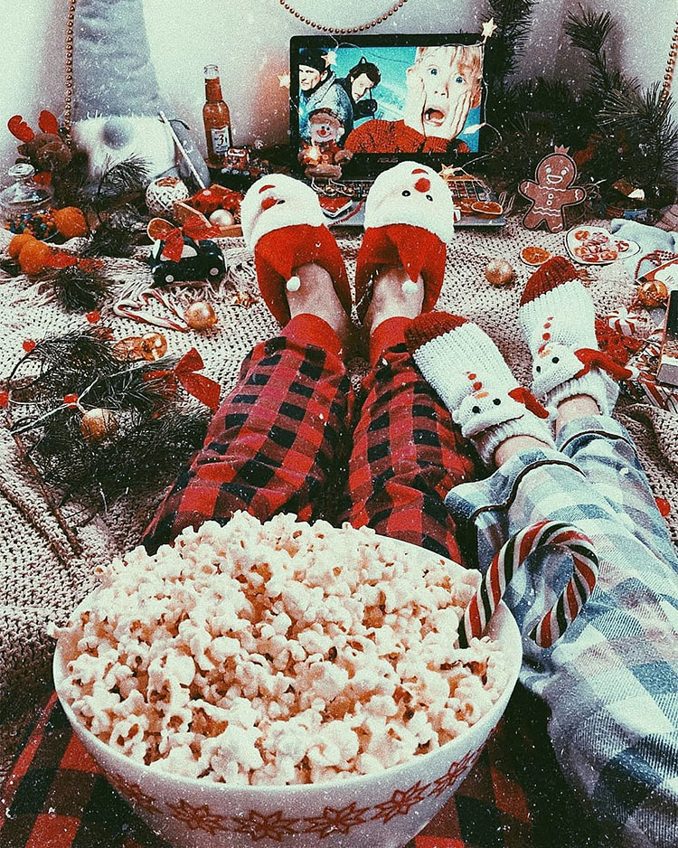COUPLE EATING POPCORN WATCHING CHRISTMAS MOVIE