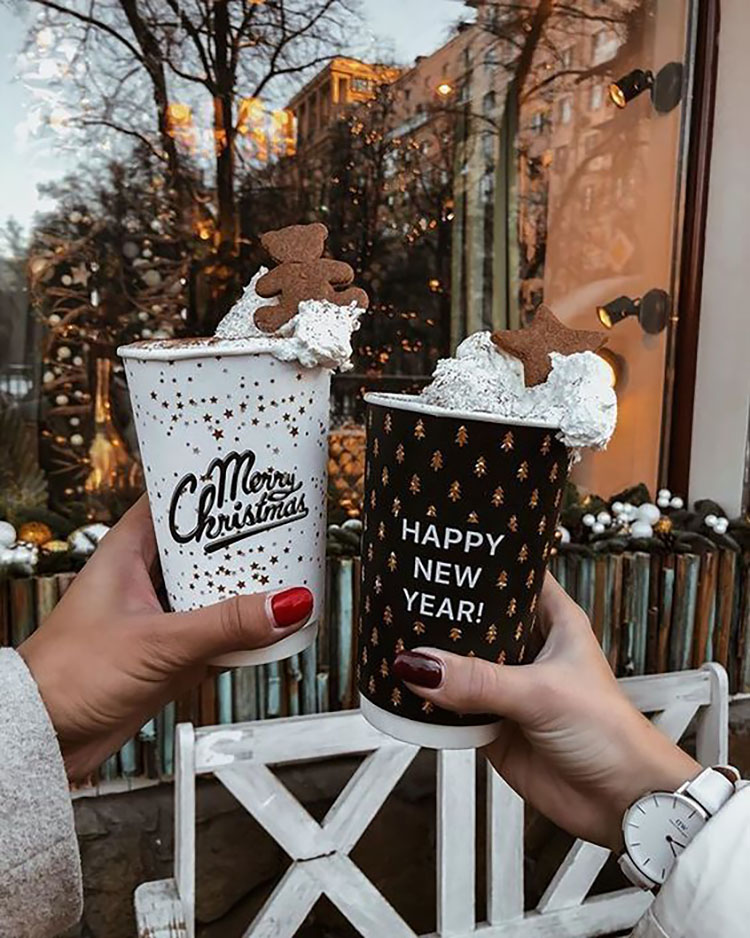 WOMEN HOLDING COFFEE CUP WITH WHIPPED CREAM
