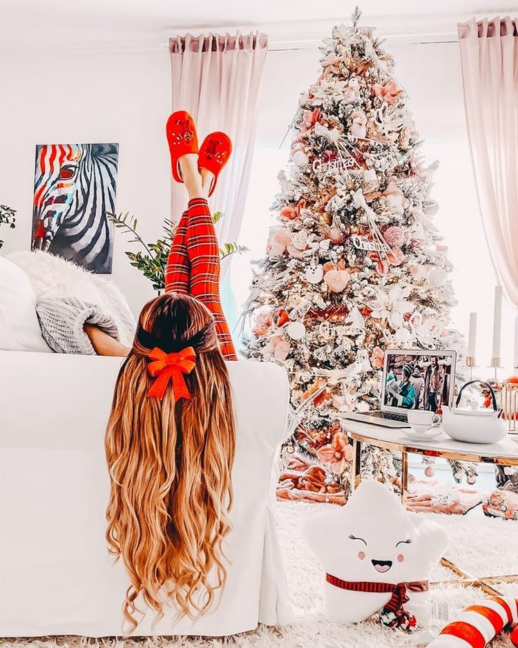 WOMEN SITTING ON COUCH LOOKING AT CHRISTMAS TREE