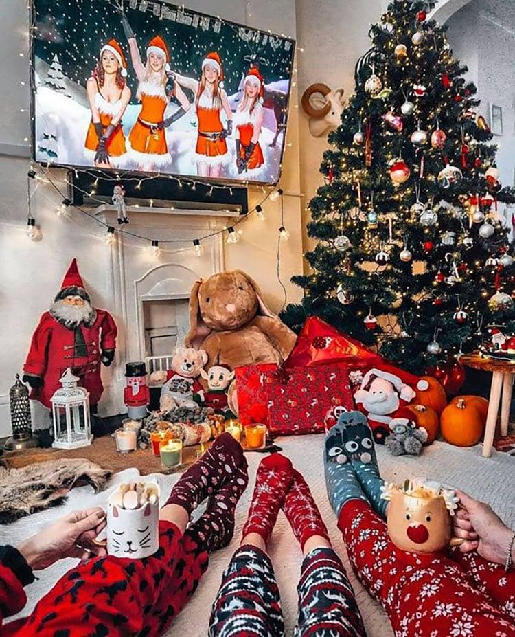 PEOPLE HOLDING MUG BY CHRISTMAS TREE