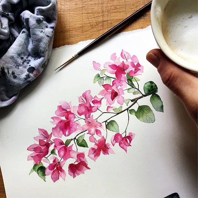 girl holding drink with watercolor flower painting