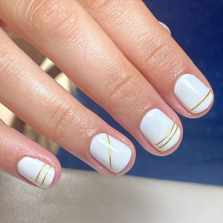white nails with gold stripes